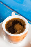 Flat lay above cup of coffee on the blue background table. Flat lay above cup of coffee on the blue background table Royalty Free Stock Image