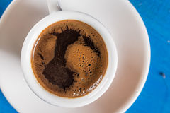 Flat lay above cup of coffee on the blue background table. Flat lay above cup of coffee on the blue background table Royalty Free Stock Photo