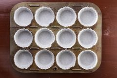Flat lay above empty white cup cakes papers containers.  Royalty Free Stock Photo