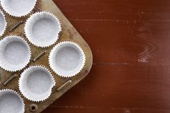 Flat lay above empty white cup cakes papers containers.  Stock Photos
