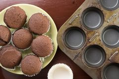 Flat lay above fresh baked chocolate cup cakes on the plate with baking tray in the background Stock Image