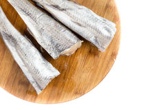 Flat lay above fresh raw hake fish on the wooden board with copy space.  Stock Photography