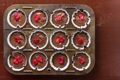 Flat lay above raw chocolate muffin pastry dough with raspberry ready for baking.  Stock Photos