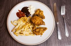 Flat lay above served meal on the white plate with kitchen utensils on the table. Fried chicken wings served with french fries, sa royalty free stock photography