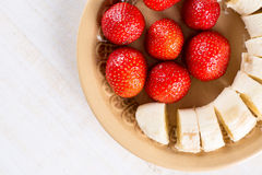 Flat lay above strawberries with sliced banana.  Stock Photo