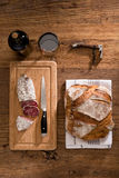 Flat lay above view of dry sausage delicatessen sliced meat with wine and traditional bread on wooden board Stock Images