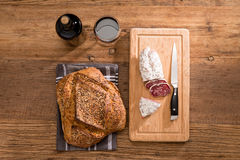 Flat lay above view of dry sausage delicatessen sliced meat with wine and traditional bread on wooden board Stock Photos