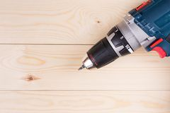 Flat lay accu cordless drill with chargeable battery on the wooden boards with copy space Stock Photography