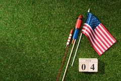 flat lay with american flagpole, wooden calendar with 4th july date and fireworks on green grass, americas independence royalty free stock images