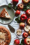 flat lay with apple pie, cake server, fresh apples and green leaves stock photo