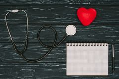Flat lay with arranged red heart, stethoscope and empty notebook on dark wooden tabletop, world health. Day concept stock images