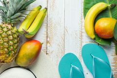 Flat Lay Arrangement Composition Tropical Fruits Pineapple Mango Bananas Green Palm Leaf Women Hat Blue Slippers on White Wood. Flat Lay Arrangement Composition Stock Photo