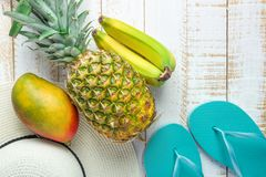 Flat Lay Arrangement Composition Tropical Fruits Pineapple Mango Bananas Women Hat Blue Slippers on White Planked Wood. Background. Vacation Traveling Royalty Free Stock Photography