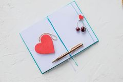Flat lay arrangement of empty notebook journal with pen next to fresh berries on white background, top view.Notebook and royalty free stock photos