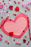 Flat lay arrangement of pink and red valentine with pencils and candy on grey background royalty free stock images