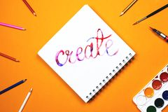 Flat lay of art supplies and notebook with colorful hand lettered sign `Create`. Concept of creativity or education Royalty Free Stock Photo