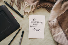 Flat lay of artist home office in bed. Handwritten inspirational quote `do small things with great love Royalty Free Stock Photos