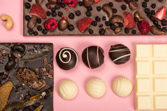 Flat lay with assorted chocolate bars with fruits and nuts and candies. Isolated on pink royalty free stock photography