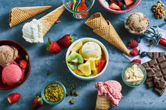 Flat lay of assorted ice cream with ingredients. Flat lay of assorted ice cream served in bowls and cones with fresh fruit and nut ingredients, choclate bar and stock photography
