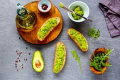 Avocado toasts with arugula. Flat lay of avocado toasts with arugula. Good fats raw healthy eating concept stock photo