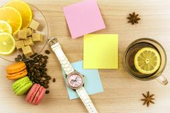 Flat lay. Beautiful ladies watch. Cup of tea with lemon. Stickers for notes, cookies macaroon. Slices of lemon and orange on a sau. Beautiful ladies watch. Cup Stock Photo