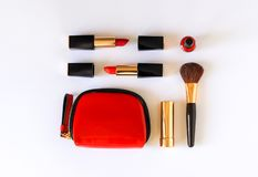 Lat lay of beauty cosmetic make up products in red, black and gold color knolled on white background. royalty free stock photography