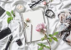 Flat lay beauty products background. Notepad, rose, perfume, mascara, watches, glasses, headphones, phone, scarf on a light backgr. Ound, top view. Beauty woman stock photos