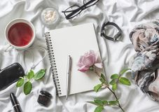 Flat lay beauty products background. Notepad, rose, perfume, mascara, watches, glasses, headphones, phone, scarf and tea on a ligh stock image