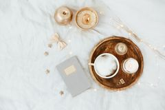 Flat Lay in bed with coffee, notebook, gold woman accessories. On grey linen stock photo