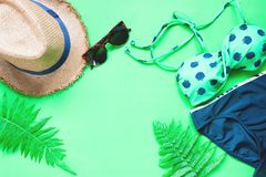 Flat lay of bikini and accessories with fern leaves on green background, Summer Stock Image