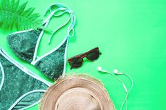 Flat lay of bikini and accessories with fern leaves on green background, Summer and Tropical concept. With copy space Stock Photo