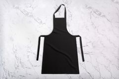 Flat lay of black apron on white marble texture. Apron on marble background. Top view royalty free stock photos