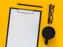 Flat lay black business accessories on yellow background with bl stock photos