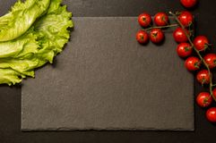 Flat lay. Black cutting board surrounded by lettuce and cherry tomatoes. Copy space royalty free stock photo