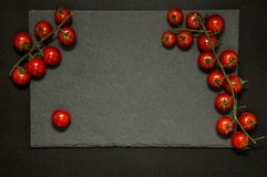 Flat lay. Black matte cutting board framed with branches of juicy cherry tomatoes. Black background. Copy space stock images