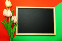 Blackboard and bunch of peony flower on red and green background flat lay royalty free stock photography