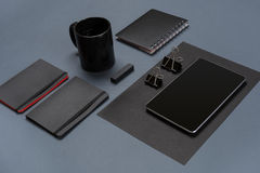 Flat lay of blank black paper sheet, black stationery items and coffee cup on gray desktop. Mock up Stock Photography