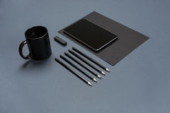 Flat lay of blank black paper sheet, black stationery items and coffee cup on gray desktop. Mock up Royalty Free Stock Photo