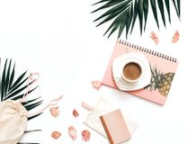 Flat lay blogger workspace mockup with tropical leaves. Coffee and accessories on white background. Copy space royalty free stock photography