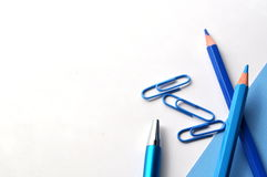 Flat lay of blue pencils, book and paper clips with copy space Stock Images