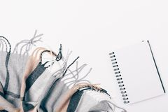Flat lay blue woolen checkered scarf with fringe. And blank open notepad on white background, top view royalty free stock images