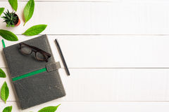 Flat lay book glasses and pen on a white wood background Stock Photo