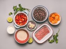 Flat lay of bowls with cooking ingredients for balanced one pan meal with beans, minced meat, rice. And various cut vegetables on gray background, top view stock photography