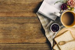 Flat lay of breakfast morning, a cup of coffee, bread and jam, and notepad on the wooden table stock photos