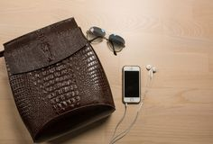 Flat lay of brown  leather backpack, earphones,  smartphone and. Sunglasses. Space for text Stock Photos