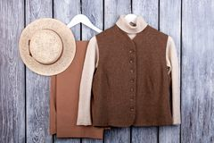 Flat lay, brown vest, trosuers and straw hat. stock photos