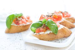 Flat lay with bruschettas with cream cheese, tomatoes and basil. Copy space Royalty Free Stock Photos