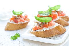 Flat lay with bruschettas with cream cheese, tomatoes and basil. Copy space Stock Images