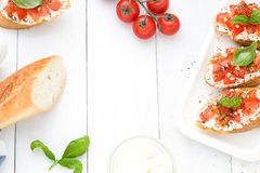 Flat lay with bruschettas with cream cheese, tomatoes and basil. Top view. Copy space Stock Images