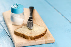 Flat lay butter spread on bread with knife and saltshaker served on a wooden board.  royalty free stock photo
